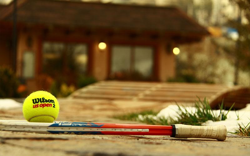 Tennisschläger und Tennisball vor dem Vereinsheim